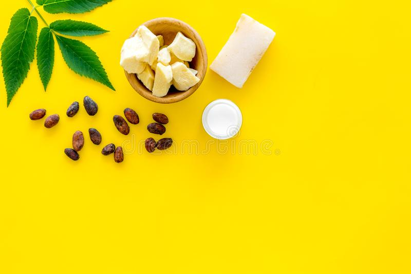 Beautiful composition with cocoa butter cosmetics. Cocoa butter and cocoa beans near homemade soap, moisturising cream. Green leaves on grey background top stock images