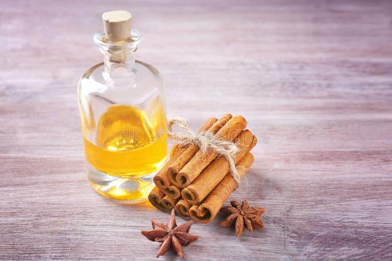 Beautiful composition with essential cinnamon oil in glass bottle royalty free stock photography