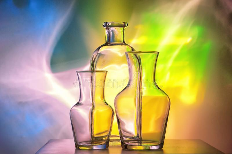 Glass transparent tableware - bottles of different sizes, three pieces on a beautiful multi-colored, yellow, blue and royalty free stock images