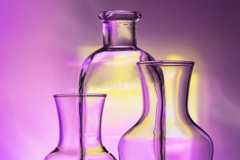 Glass transparent tableware - bottles of different sizes, three pieces on a beautiful multi-colored, yellow, lilac and royalty free stock photos