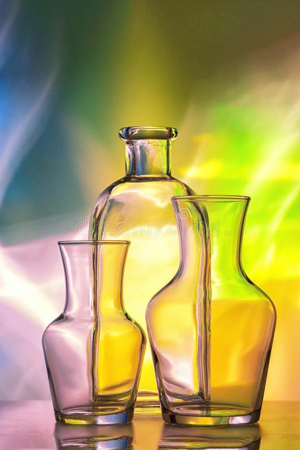 Glass transparent tableware - bottles of different sizes, three pieces on a beautiful multi-colored, yellow, blue and royalty free stock image