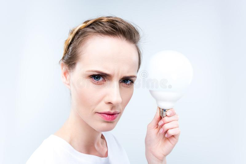 Woman with light bulb. Beautiful concentrated woman holding light bulb, isolated on white stock images