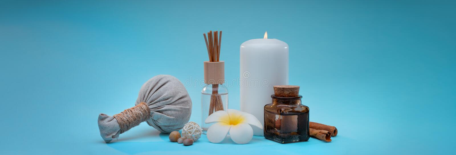 Beautiful and concise spa composition on turquoise background. Beautiful and concise spa composition with a candle, frangipani flower, oil bottle, herbal ball royalty free stock image