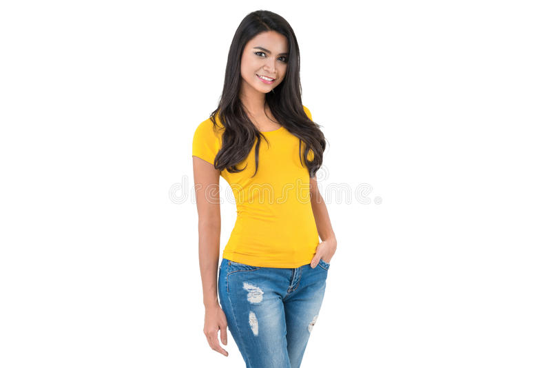 Beautiful confident Asian woman in plain yellow t-shirt and blue. Jeans posing with hand in pocket on white background stock photography