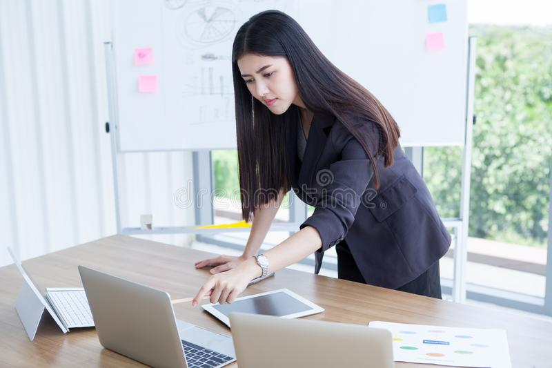 beautiful Confident asian young business woman working and pointing laptop computer with tablet and document file graph on desk stock photo