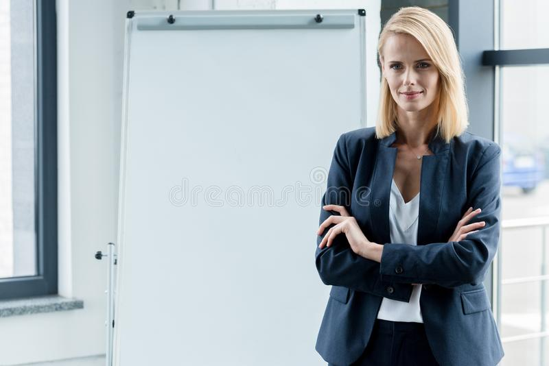 Beautiful confident businesswoman standing with crossed arms and smiling at camera. In office stock photo