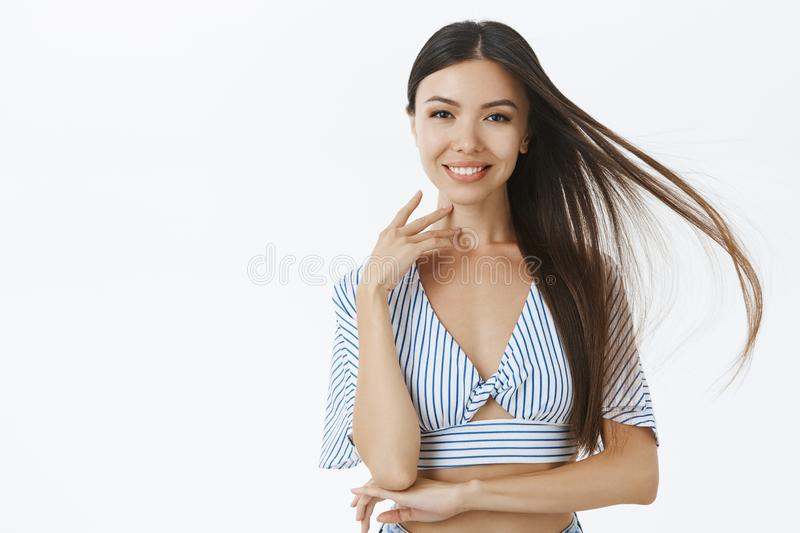Beautiful confident and delighted asian female in cropped blouse touching face gently and smiling standing over gray stock photos