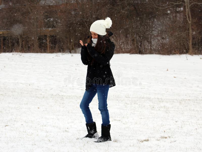 Beautiful confident green eyes teenager walking under snow while snowing. In Michigan. Gorgeous 14 years old teen. Happy smiling daughter stock photography