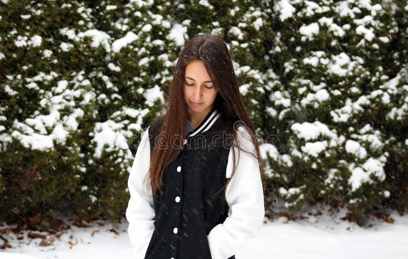 Beautiful confident green eyes teenager walking under snow while snowing. In Michigan. Gorgeous 14 years old teen. Happy smiling daughter stock image