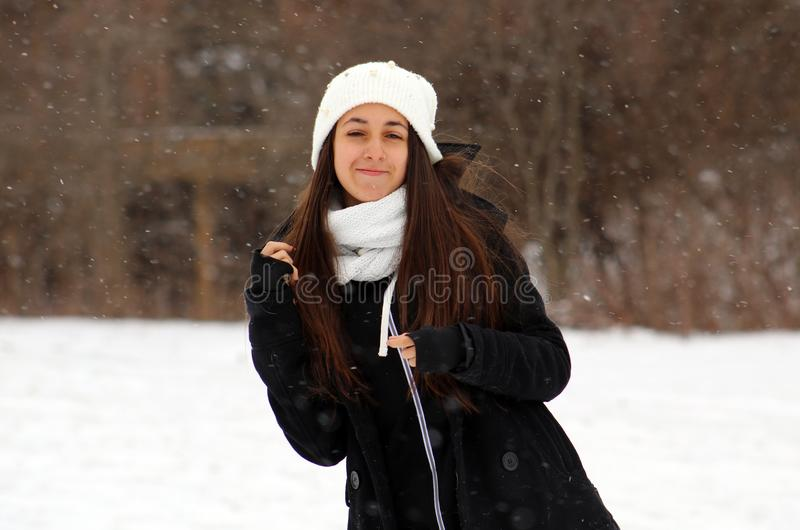 Beautiful confident green eyes teenager walking under snow while snowing. In Michigan. Gorgeous 14 years old teen. Happy smiling daughter royalty free stock photos