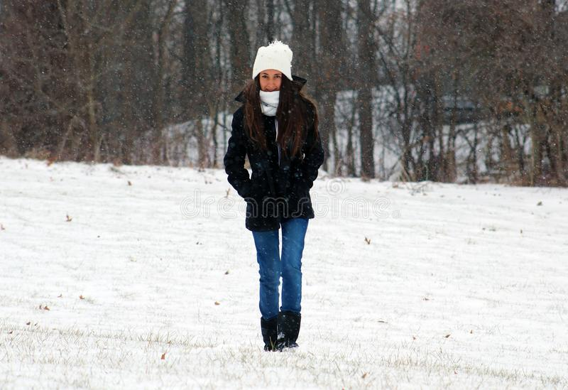 Beautiful confident green eyes teenager walking under snow while snowing. In Michigan. Gorgeous 14 years old teen. Happy smiling daughter stock photo
