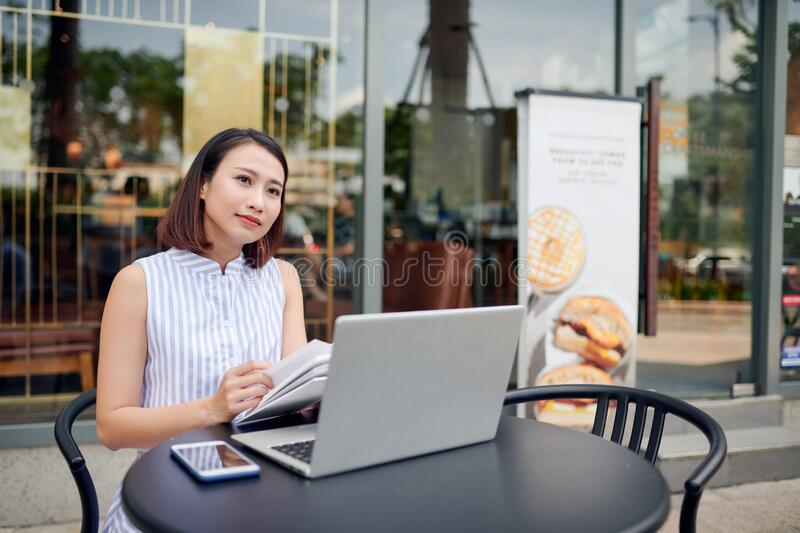 Beautiful confident woman in casual clothing reading book and drinking coffee while sitting in cafe with laptop and notebook.  royalty free stock photos