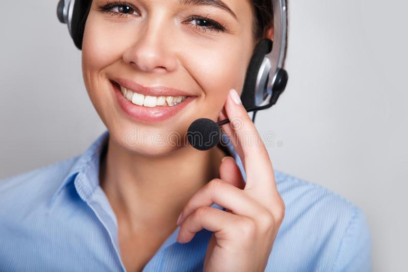 Customer support phone operator in headset, with blank copyspace area for slogan or text message, over grey background royalty free stock photos