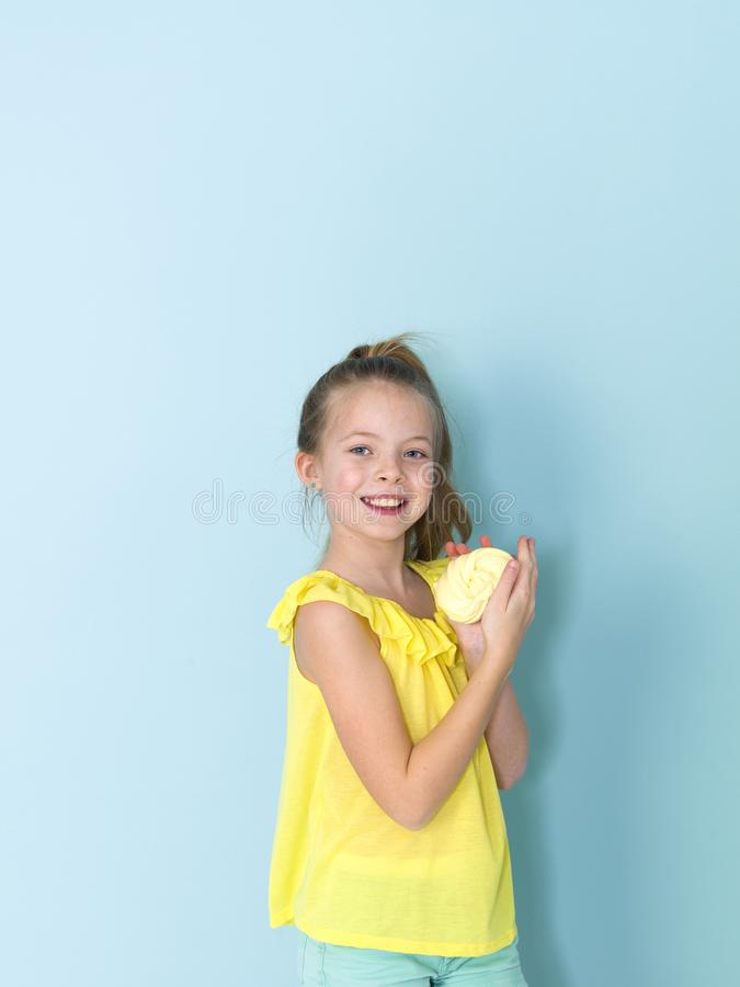 Beautiful and cool and blond 9 year old girl is playing with yellow slime in front of blue background royalty free stock photo