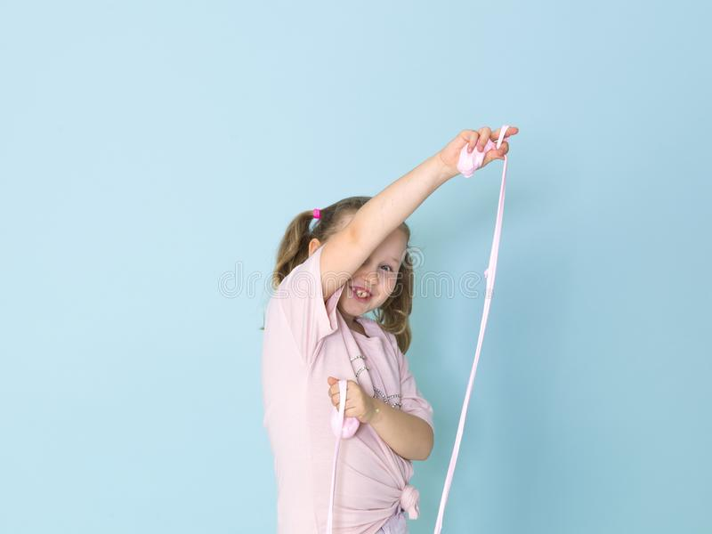 Beautiful 8 year old girl is playing with pink slime in front of blue background stock photography