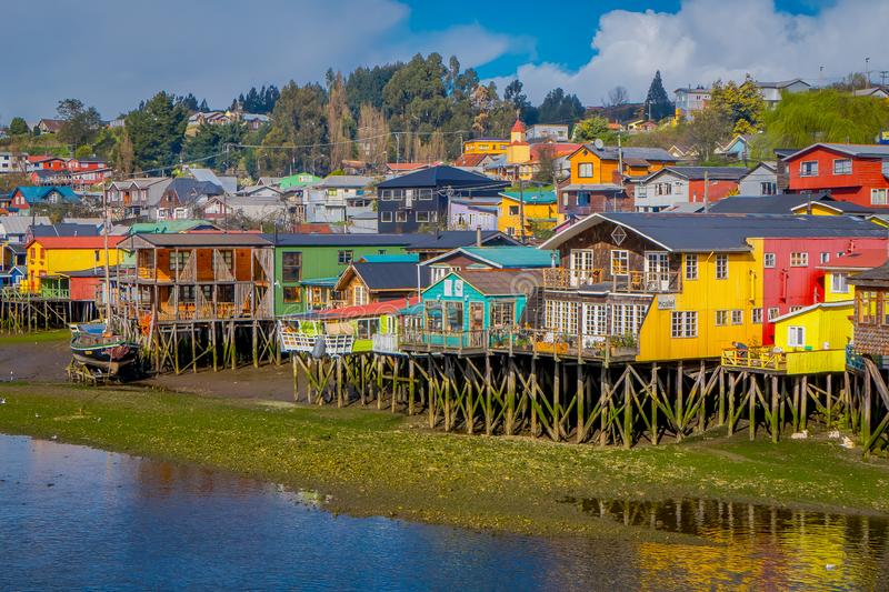 Beautiful coorful houses on stilts palafitos in Castro, Chiloe Island. Chile, in front of stagnant water in gorgeous blue sky royalty free stock photography