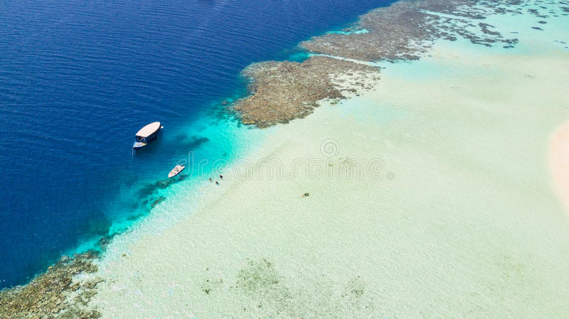 Beautiful coral reef with anchoring boats stock photography