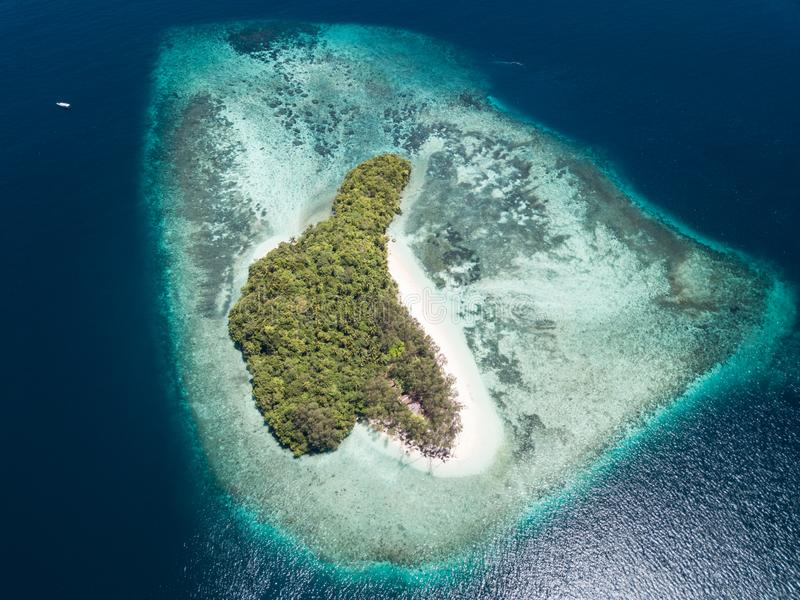 Aerial View of Remote Island and Reef in Raja Ampat. A beautiful coral reef fringes a idyllic island in Raja Ampat, Indonesia. This remote, tropical region is royalty free stock photos