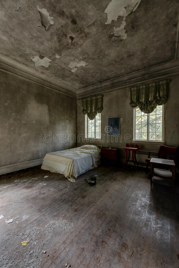 Twin Bed with Windows, Valances & Hardwood Floors - Abandoned Mansion. A beautiful corner twin bed surrounded by plastered walls, windows with valances and royalty free stock photos