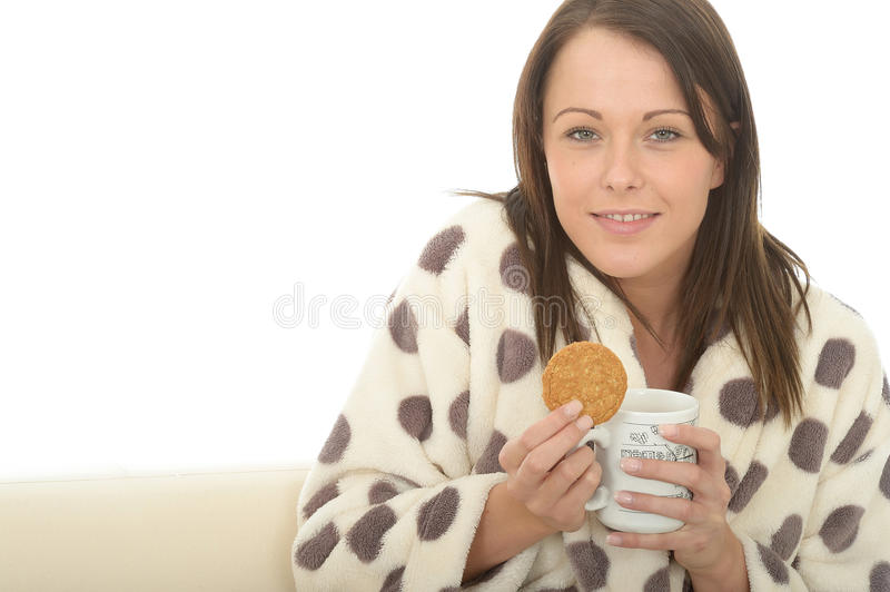 Beautiful Cosy Relaxed Young Woman In A Dressing Gown Enjoying Tea And Biscuit royalty free stock photos