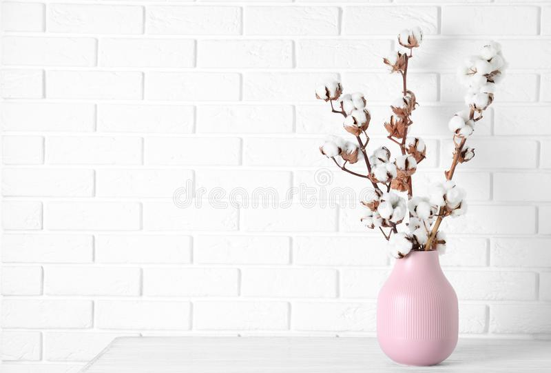 Beautiful cotton flowers in vase on wooden table against white brick wall stock photos