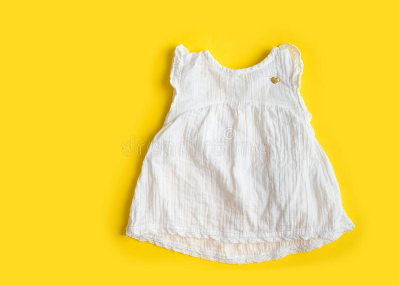 Beautiful cotton muslin vintage baby girl white dress on yellow background - summer royalty free stock images