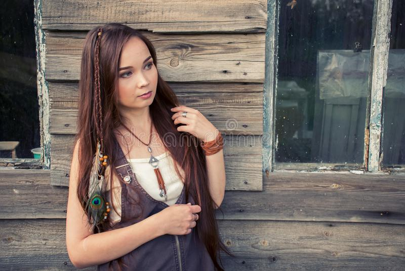 Beautiful country boho girl stands on the background of an old wooden house with windows stock photo