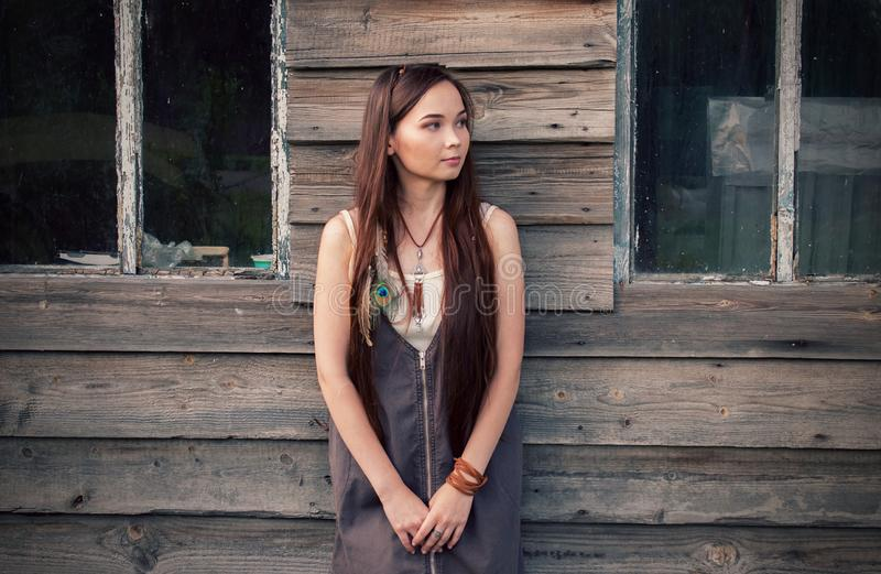 Beautiful country boho girl stands on the background of an old wooden house with windows stock images