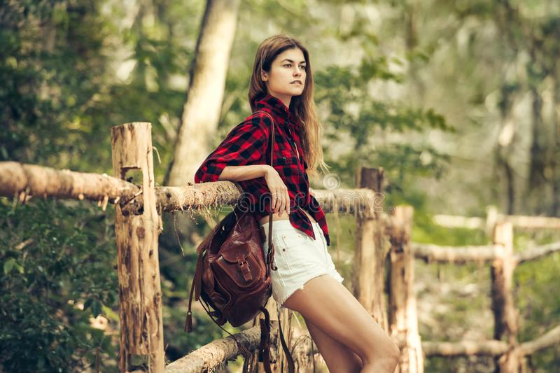 Beautiful country girl traveling and waiting near wooden fence wearing red checkered t-shirt, shorts and leather brown backpack stock photography