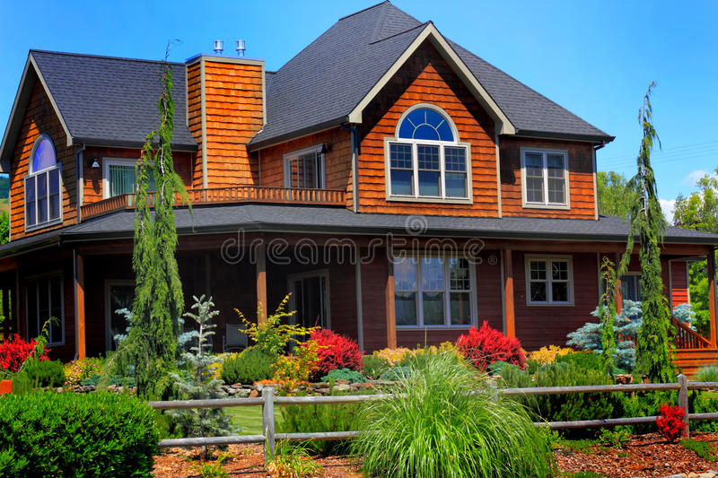 Beautiful Country Home. A beautiful large redwood country home, a wide open porch and decking. Full landscaping with rustic rail fence stock photos