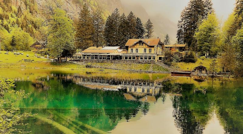 Beautiful country house in the middle of a green scenery reflecting in the lake in Switzerland. A beautiful country house in the middle of a green scenery royalty free stock photography