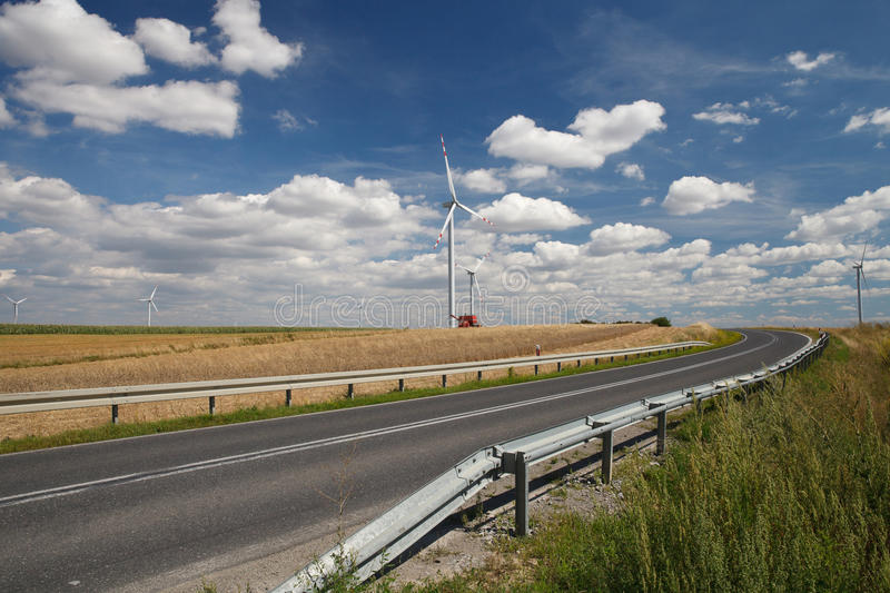 Beautiful countryside landscape: field, wind turbines and the road. Europe royalty free stock photos