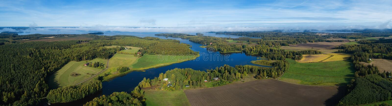 Beautiful countryside landscape with fields, river, forest and huge lake. Aerial panorama of Finland on autumn. royalty free stock photo