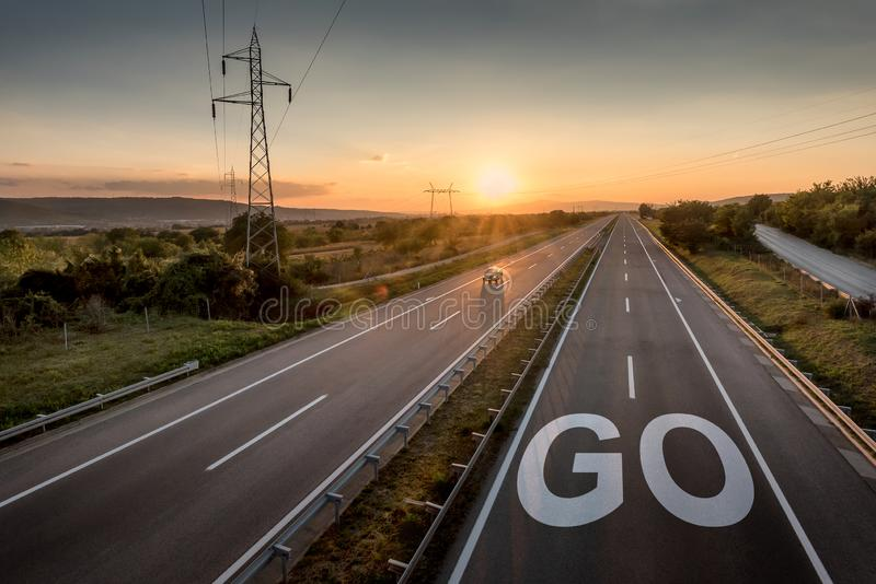 Beautiful Motorway with a Single Car at sunset with motivational message Go stock photos