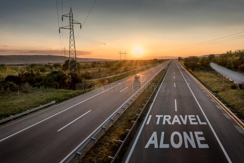 Beautiful Motorway with a Single Car at sunset with motivational message I Travel Alone royalty free stock photo