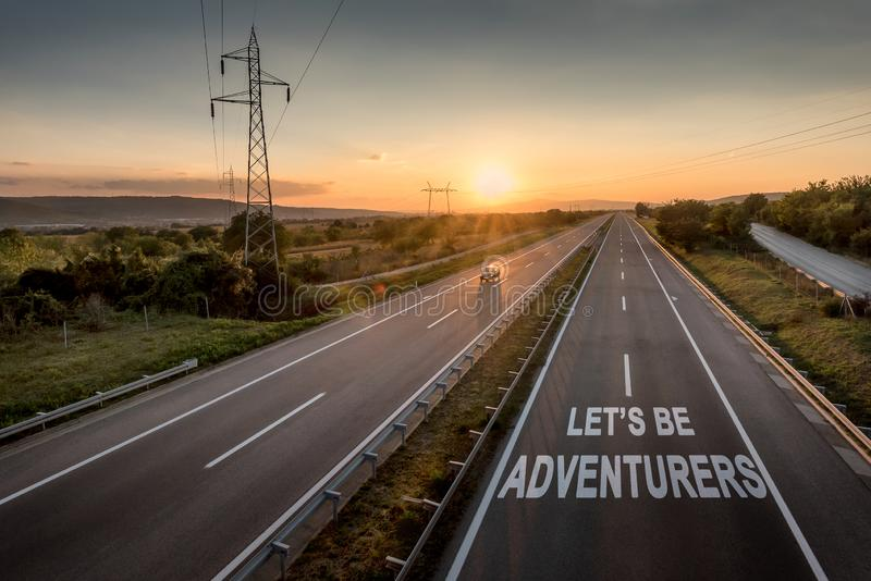 Beautiful Motorway with a Single Car at sunset with motivational message Let`s Be Adventurers. Beautiful Countryside Motorway with a Single Car at sunset with stock photography