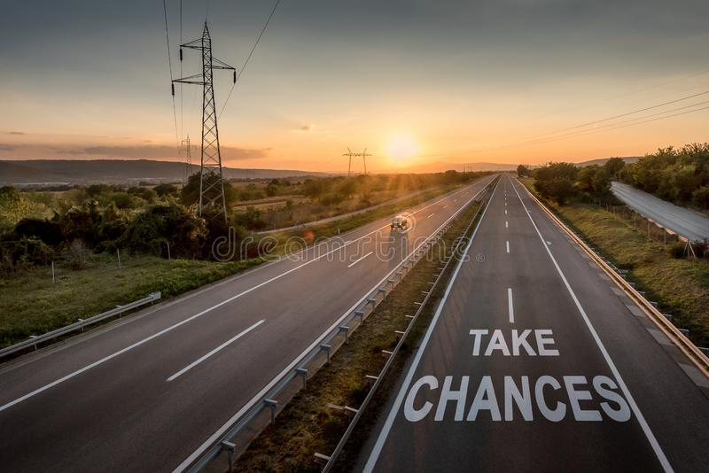 Beautiful Motorway with a Single Car at sunset with motivational message Take Chances stock photography