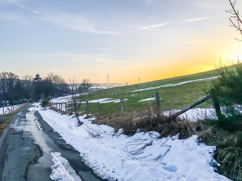 Beautiful countryside road with melting snow and green hill at sun dawn in Germany Hochsauerland royalty free stock images
