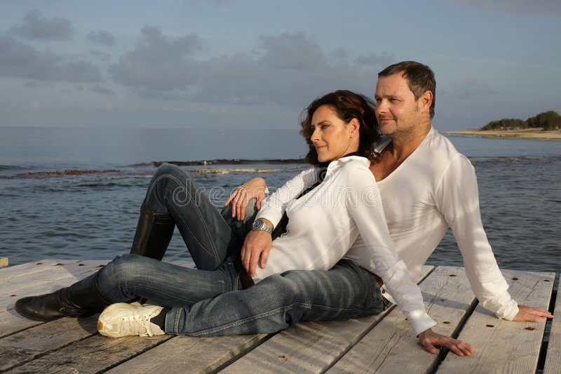 Beautiful couple. On a pier looking into the distance royalty free stock images
