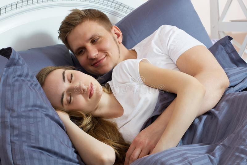 Beautiful couple in bed . Guy gently wakes his girlfriend in bed in the morning stock photos
