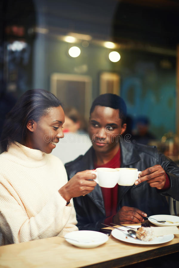 Beautiful couple clinking cups while smiling sitting in coffee shop royalty free stock photos