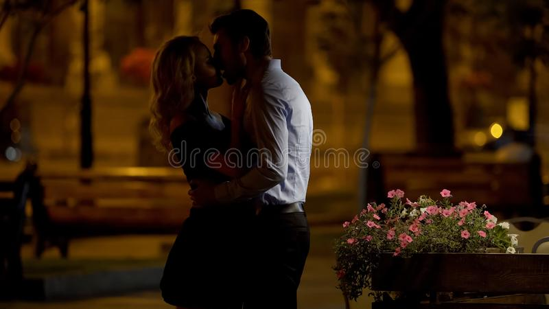 Beautiful couple cuddling and kissing tenderly in park, evening date, love stock photos