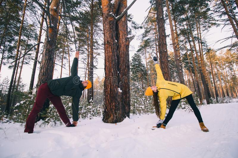 Couple in doing workout or yoga together in winter park. Beautiful couple in doing workout or yoga together in winter park among snow covered trees, healthy royalty free stock image