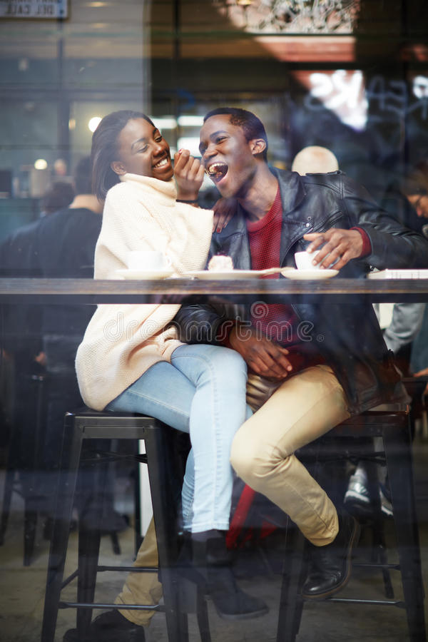 Beautiful couple drinking coffee and laughing happily. Happy stylish friends having coffee together, laughing young couple in cafe, having a great time together royalty free stock images