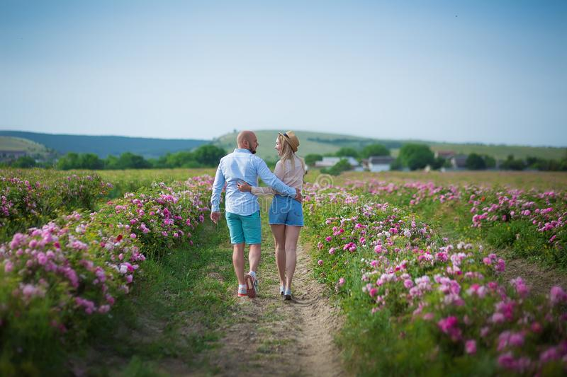 Beautiful couple in field, Lovers or newlywed posing with perfect blue sky on roses field on background wearing jeans and retro stock image