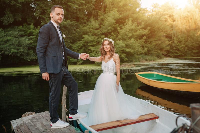 Beautiful couple groom and bride near river boat. Against the background of beautiful nature and sunset royalty free stock image