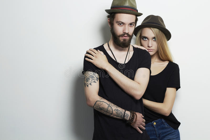 Beautiful couple in hat together. Hipster boy and girl. Bearded young man and blonde. Tattoo. Fashion beautiful couple in hat and posing over white background stock image