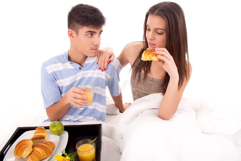 Beautiful couple having breakfast lying in the bed