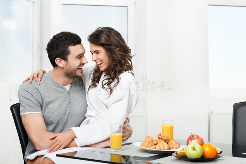 Beautiful couple having breakfast. Table, girl sits on hands for a boyfriend stock images