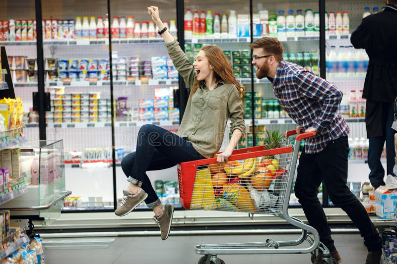 Beautiful couple having fun while choosing food in the supermarket. Happy couple having fun while choosing food in the supermarket. Young happy men pushing royalty free stock photography